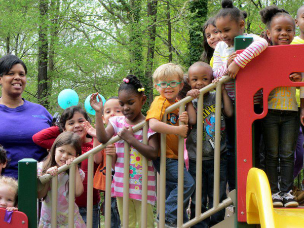 Students and their families celebrate at the ribbon cutting ceremony for the Raleigh preschool's new playground.